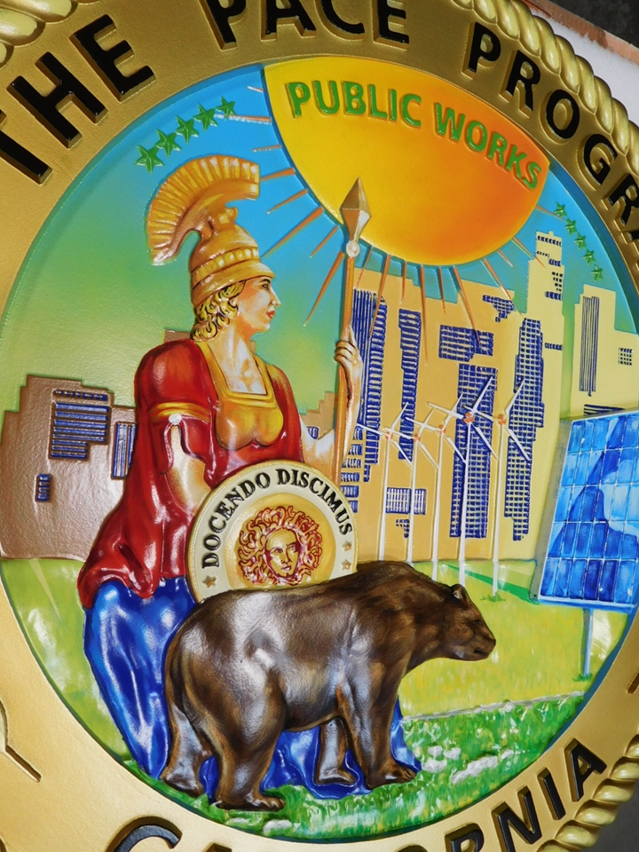 BP-1033- Close-Up Photo of Carved Plaque of the Seal of the PACE Program, 3-D Artist-Painted