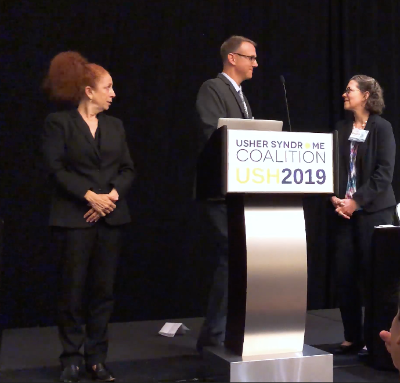 """Dr. Marly Kenna stands on stage with Mark Dunning behind a lectern with the sign """"Usher Syndrome Coalition USH2019"""". A platform interpreter looks on at Mark and Marly."""