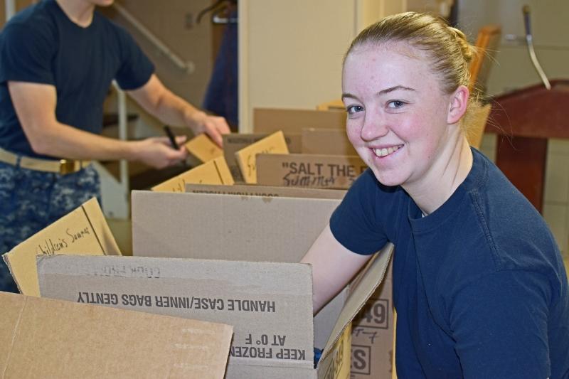Midshipman 4th class Kelli McQuiston packs boxes.
