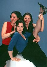 BRECHT ON BRECHT - 2002. A group of women that are having a great time. One person is wearing a red shirt. The second person is wearing a blue shirt and she has her leg in the air. The last person is wearing a black dress. They are posing for the photo.