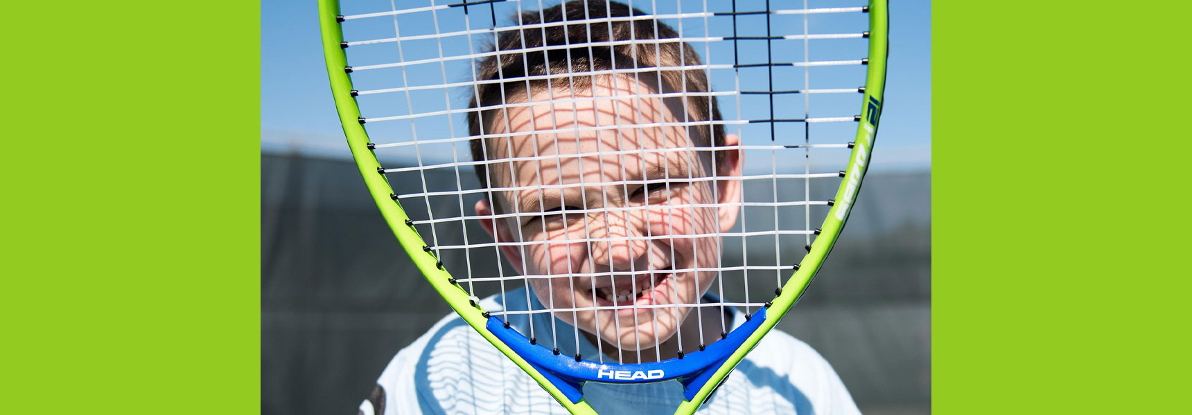 Young boy looking through a tennis racket