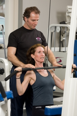 PTP franchise Certified Personal Trainer assisting client with a lat pull down exercise