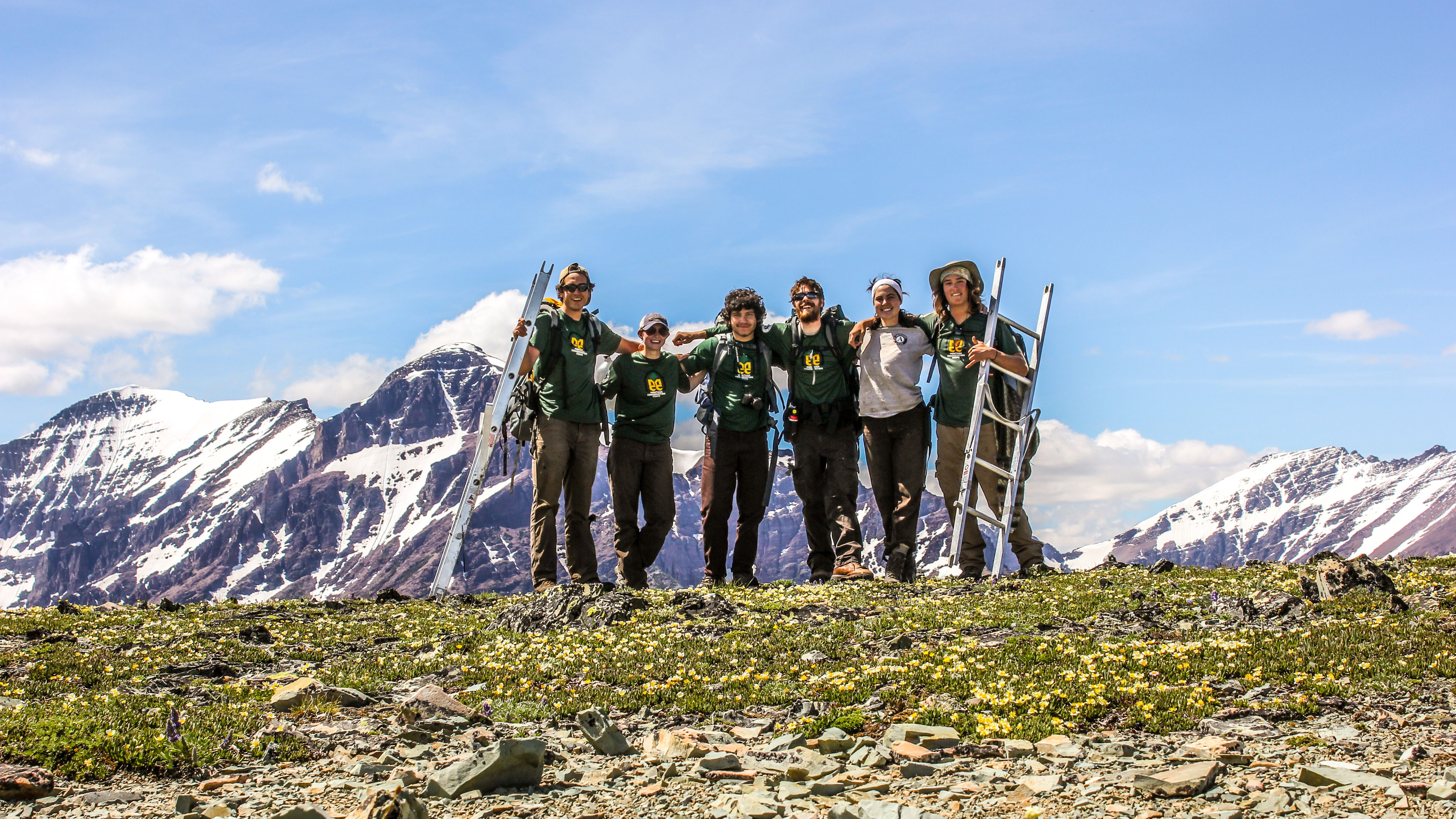 Six diverse crew members wearing MCC and AmeriCorps t-shirts and standing on a high mountain with a couple of ladders and it is sun shining day but the mountain peaks are covered in snow.