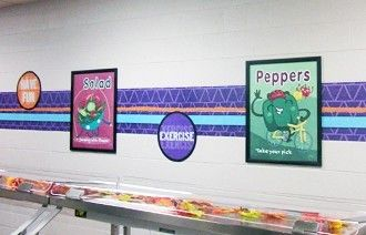 2 food character posters in a frame on a school wall, nutrition education posters