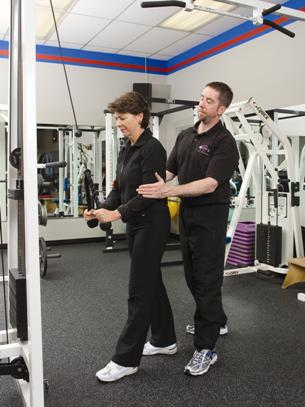 PTP New Canaan personal fitness trainer assisting a client with lat pulldown exercises