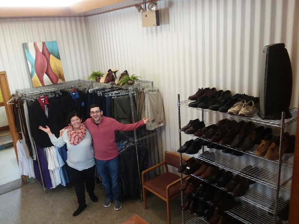 A woman and teenage son stand in front of racks of clothing, smiling, with their arms out to proudly display their work.  The racks are nicely organized with dress shoes, suits, and other items.