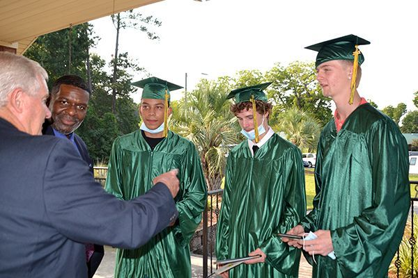Board Chair Larry Hewett speaks with the summer graduates at Thomas Academy Principal George Ward looks on.