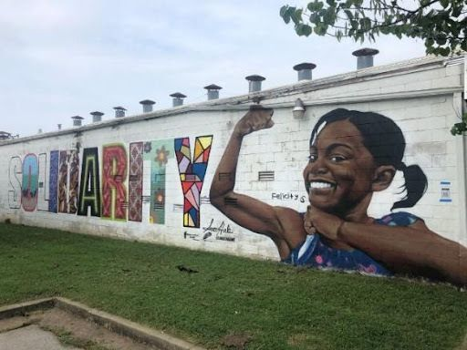 Solidarity: A mural stretches across the side of a white building. Stark block letters spelling out the word Solidarity are filled with different vibrant designs in each letter. A young Black girl in a blue dress is painted at the end of the word, flexing