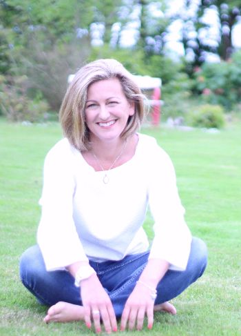 Photo of Carol Brill smiling while sitting on grass