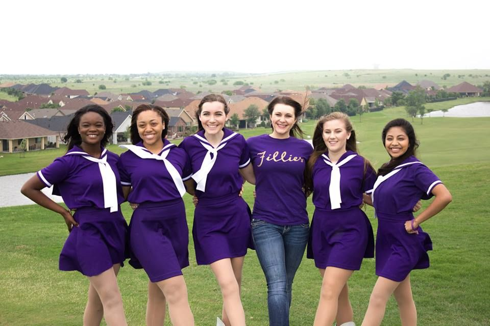 Denton High School drill team members posing on a golf course