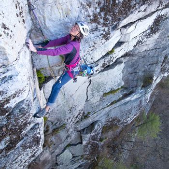 Lynn McGrew balances with a wide stance on the cliff while looking up