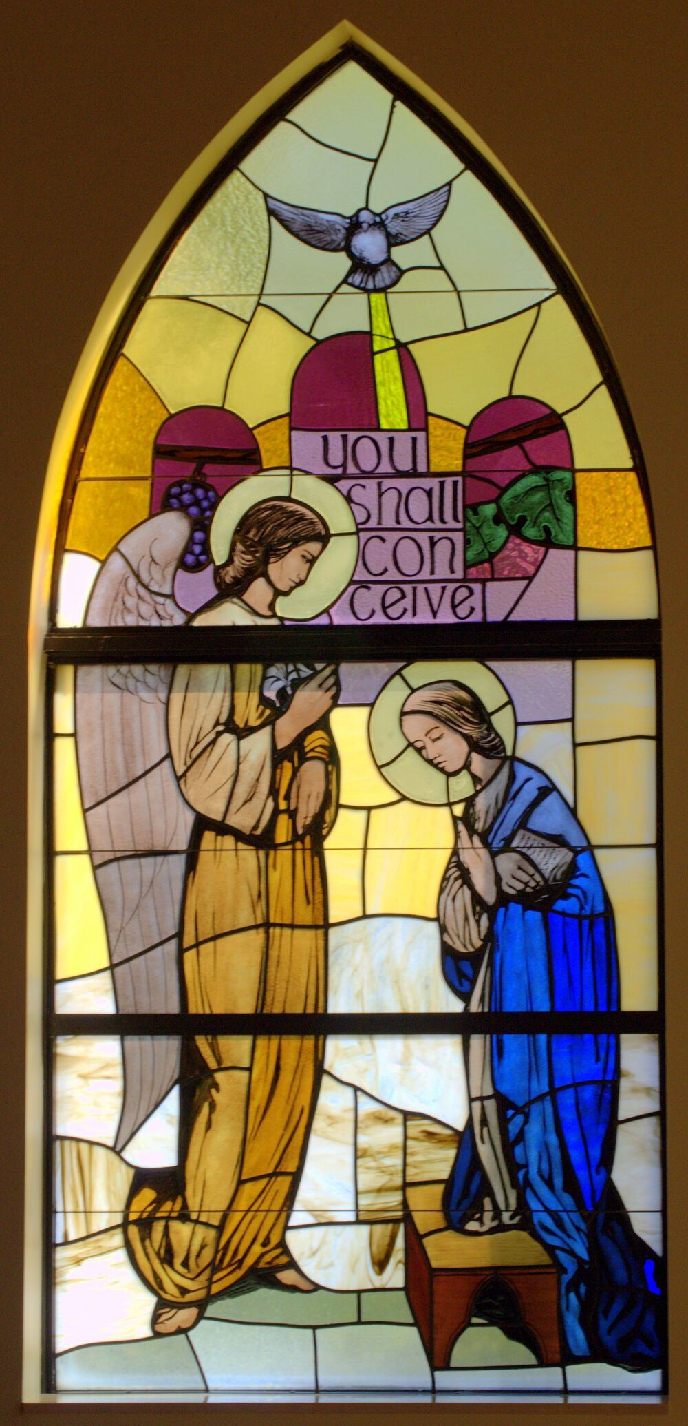 Gabriel announces to Mary that she will conceive the Son of God in this window at St. Patrick's Church, Palm Beach Gardens. The Holy Spirit overshadows her as a dove.