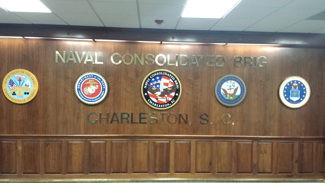 V31195 - All Four Service Seal wall plaques, with Navy Consolidated Brig crest plaque mounted in center.