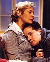 Karen Case Cook and Ben Rauch. Both people are hugging and they have serious faces. Karen is wearing a grey blouse and Ben is wearing a blue jacket.