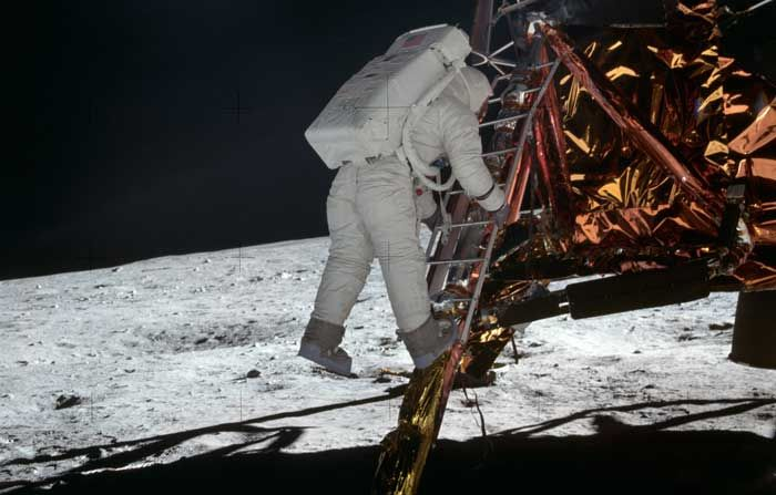 Astronaut Edwin E Aldrin Jr, Lunar Module LM pilot, climbs down the LM ladder, preparing for his first steps on the moon.
