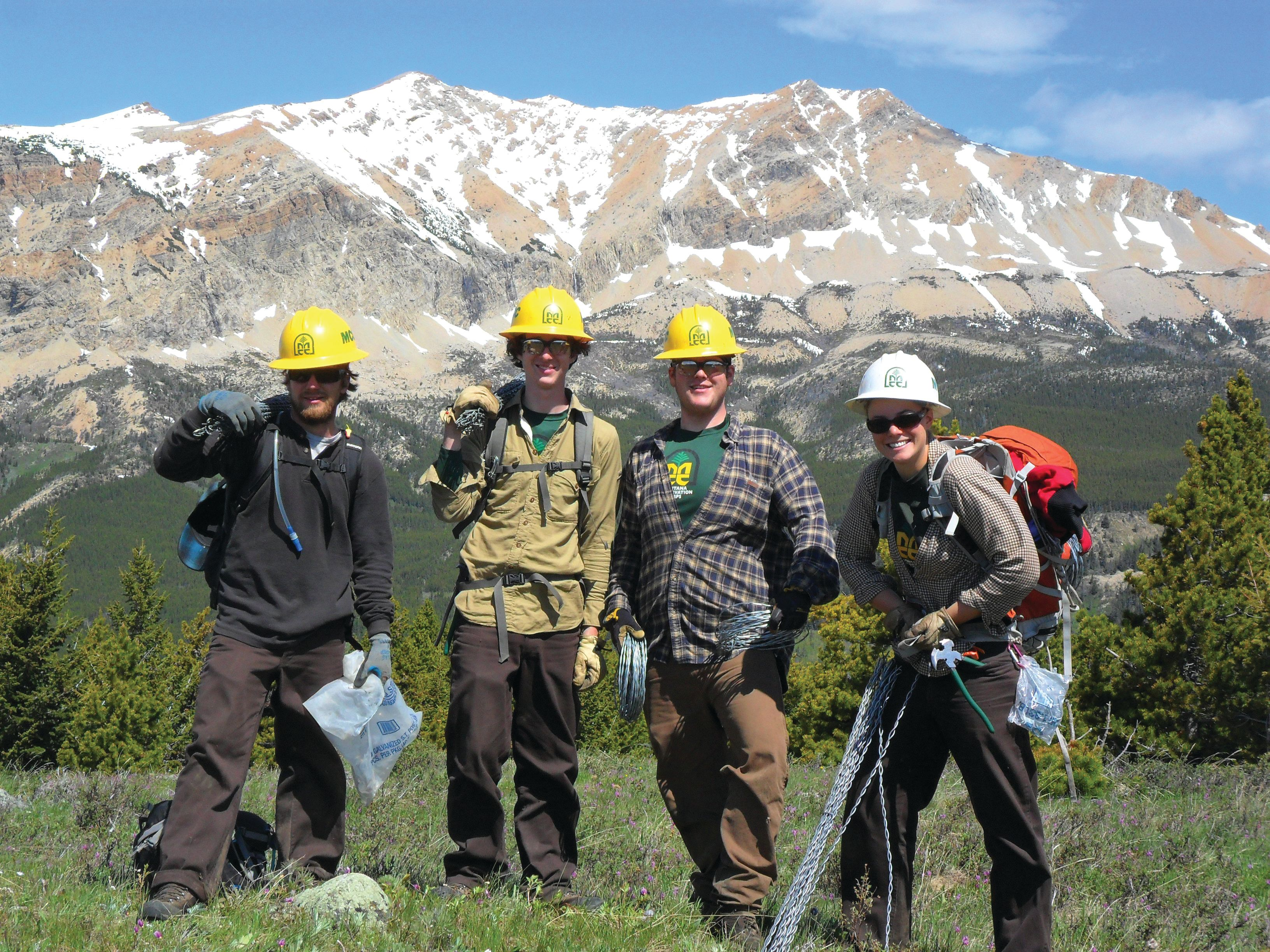 beautiful white capped mountain with 3 young men in yellow MCC helmets and a female in a white helmet signifying she is the crew Leader