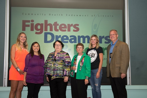 Six people stand in front of the fighters, dreamers, and doers logo.