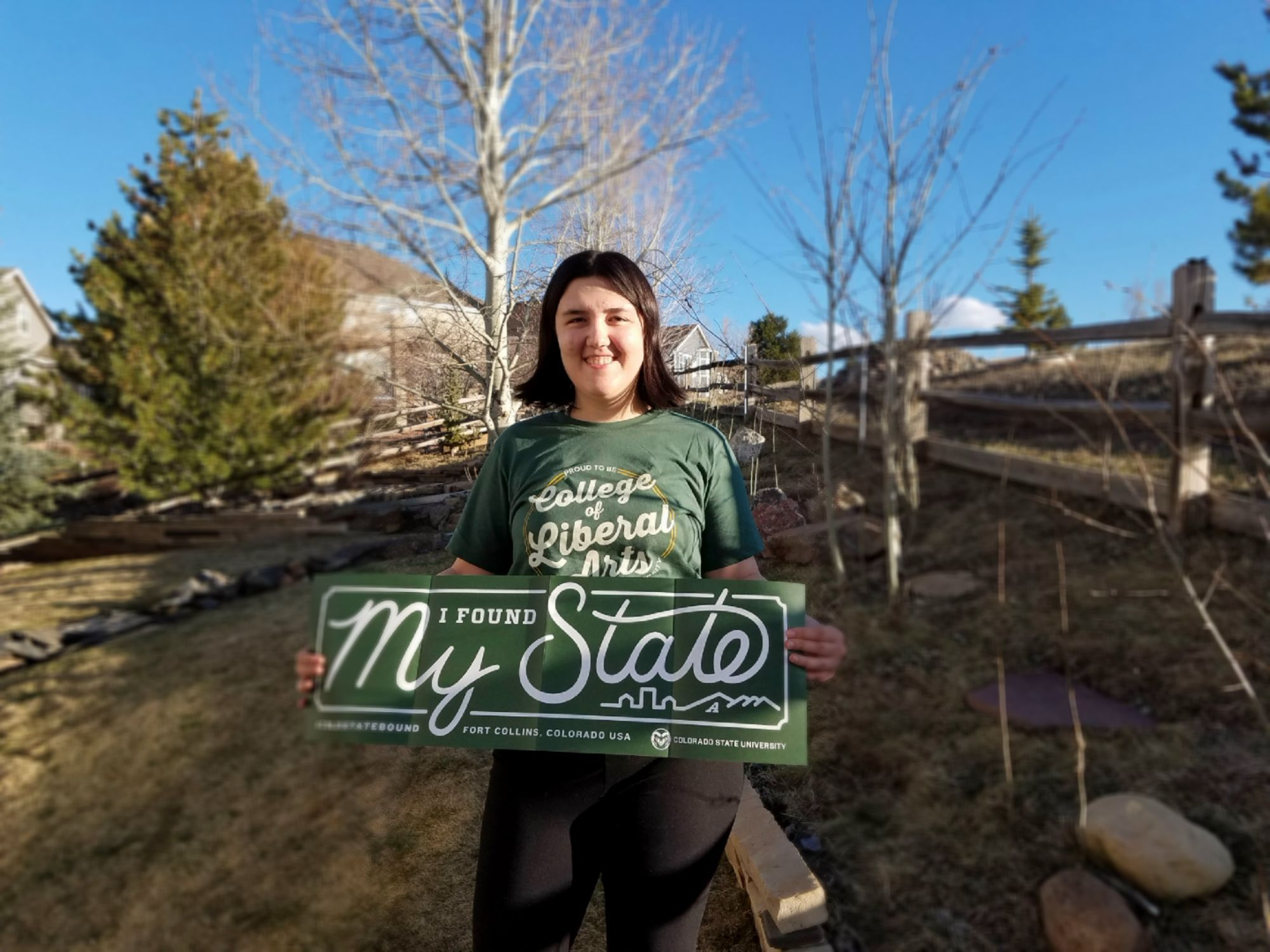 Woman stands outside with green sign reading I found my state