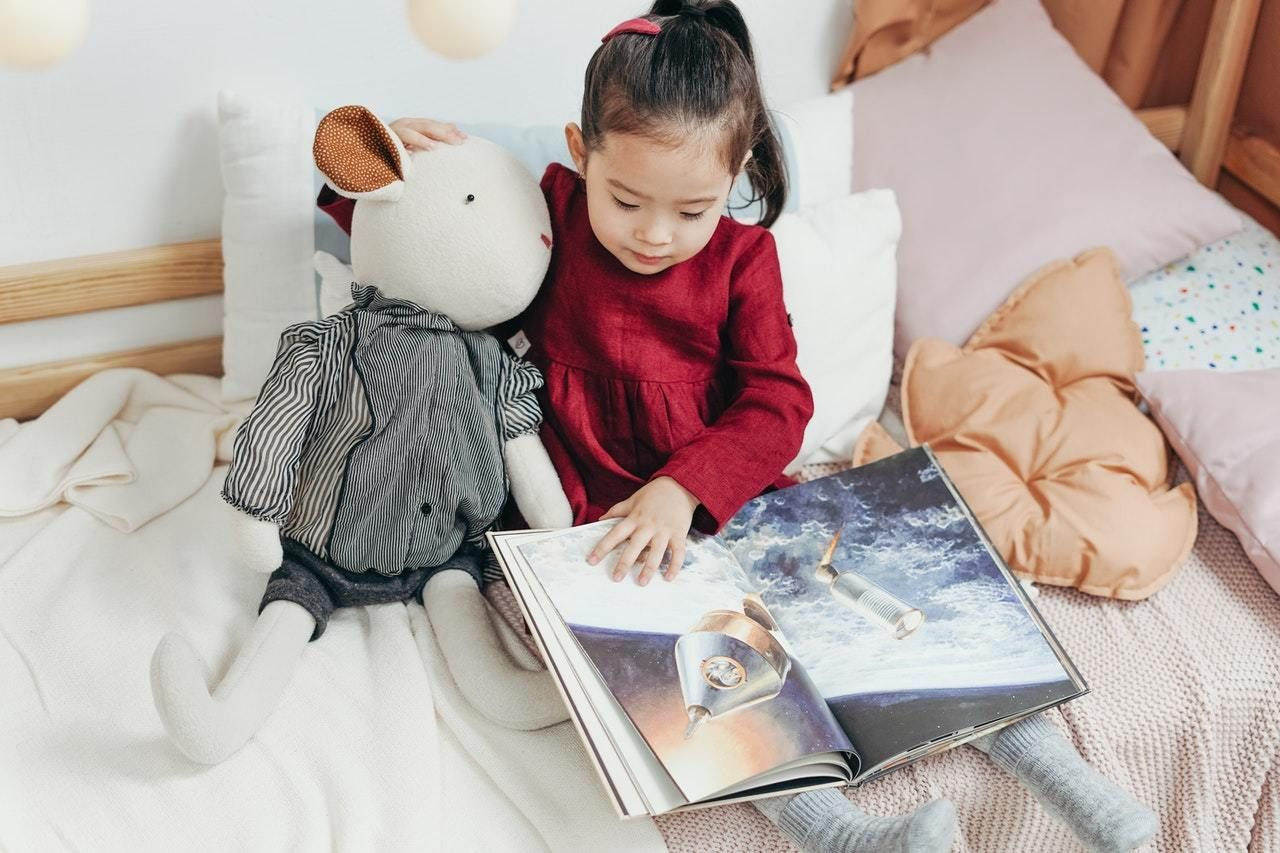 Little girl in red shirt reading a picture book about rockets in bed while cuddling an oversized mouse stuffed animal