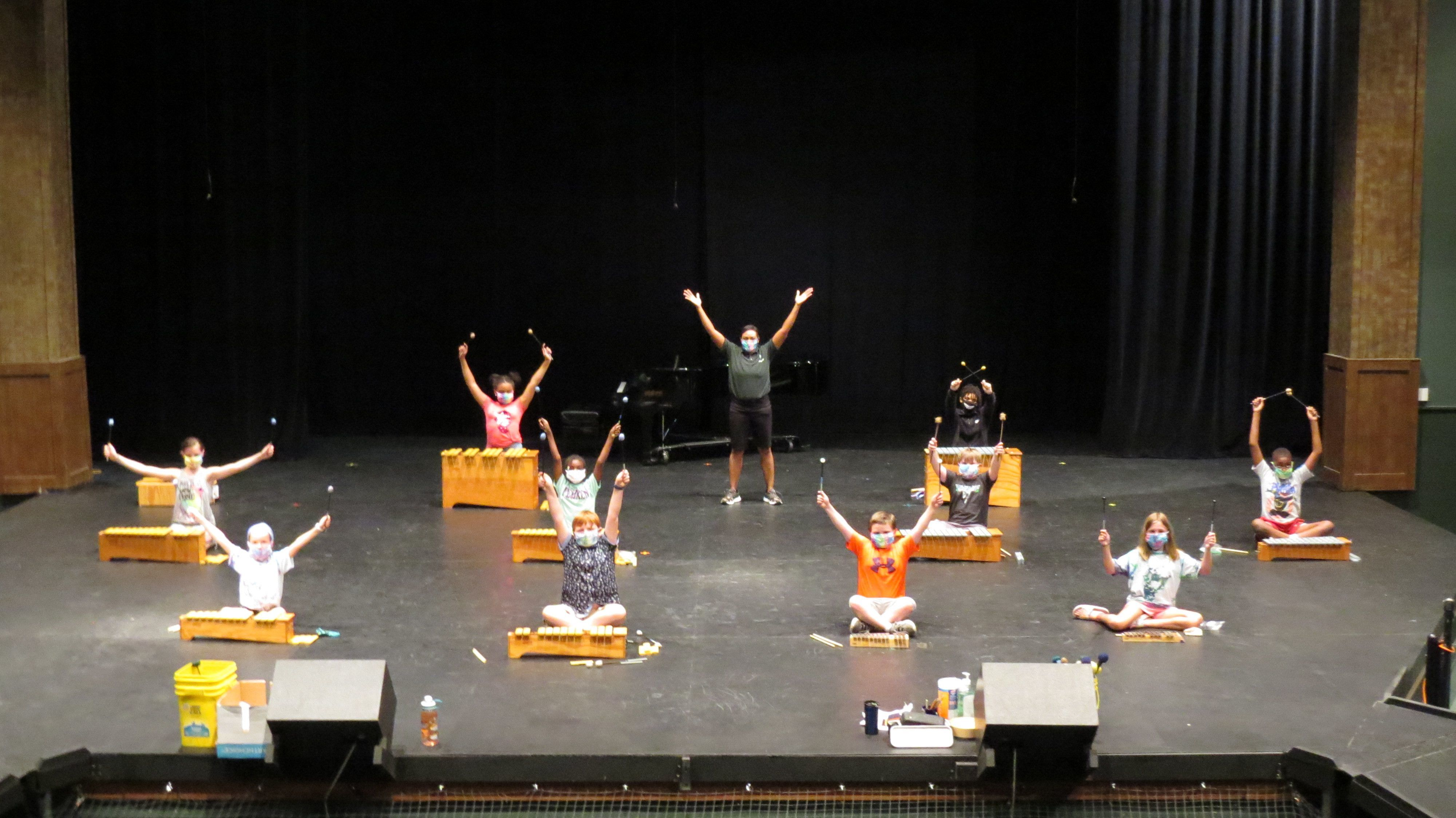 A socially distanced group of elementary aged students and their instructors pose on a large stage with their orff instruments