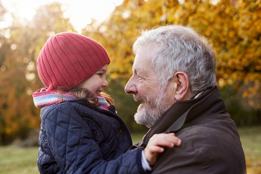 Grandfather holding 4-year-old granddaughter outside during the fall, both are smiling