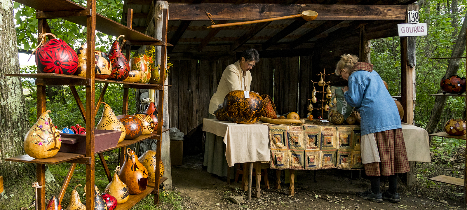 Two women work in a booth filled with decorated gourds for sale.