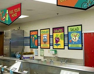 School serving line showing 4 food posters of food characters, nutrition education, school signs
