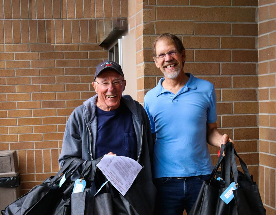 two older men smiling while holding bags to deliver meals for meals on wheels