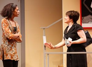 (L to R): Felice is standing, wearing a mustard blouse. Anita is standing and facing Felice, wearing a black dress and holding a black handbag on one of her shoulders. She's using a hand gesture in the other one while speaking to Felice.