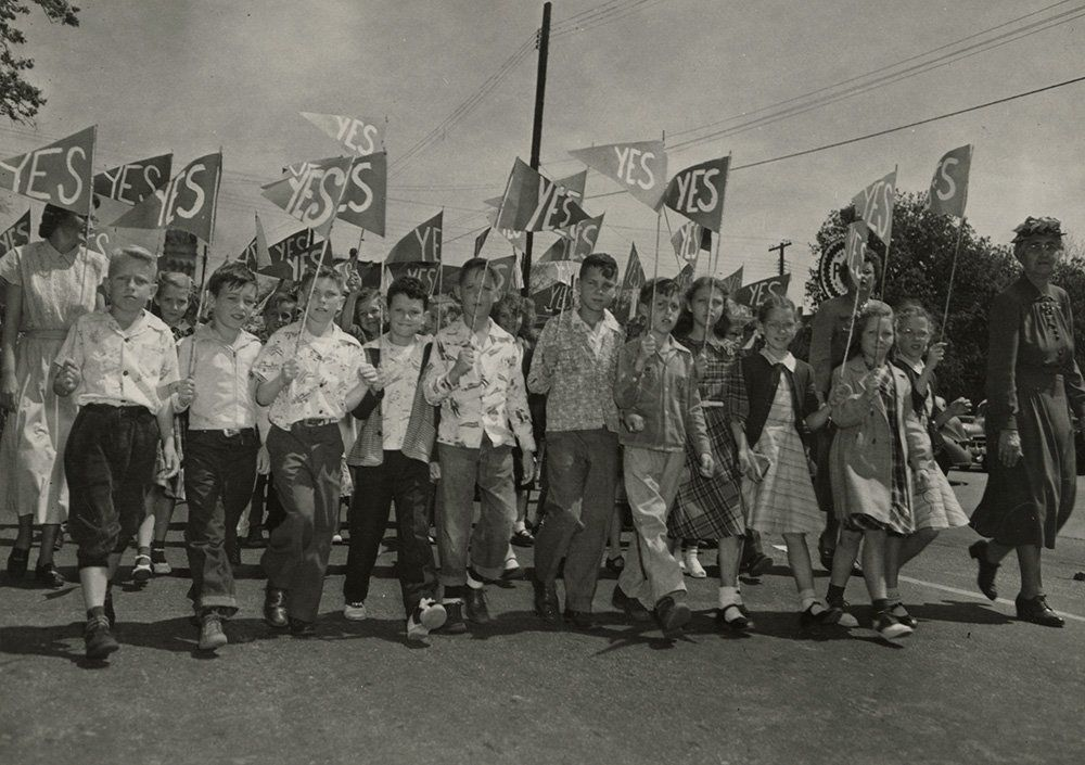 Fox Elementary School students march in parade encouraging voters to approve consolidation of Columbus and Muscogee County schools, 1949