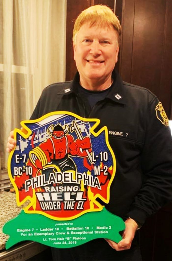 X33891- Firefighter Holding the  Carved 2.5-D HDU Plaque of theLogo  Shoulder Patch  of the2nd and York Station, Philadelphia Fire Department