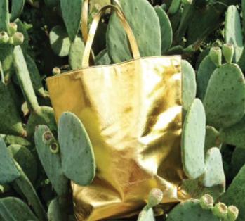 Yellow bag lying on top of a cactus.