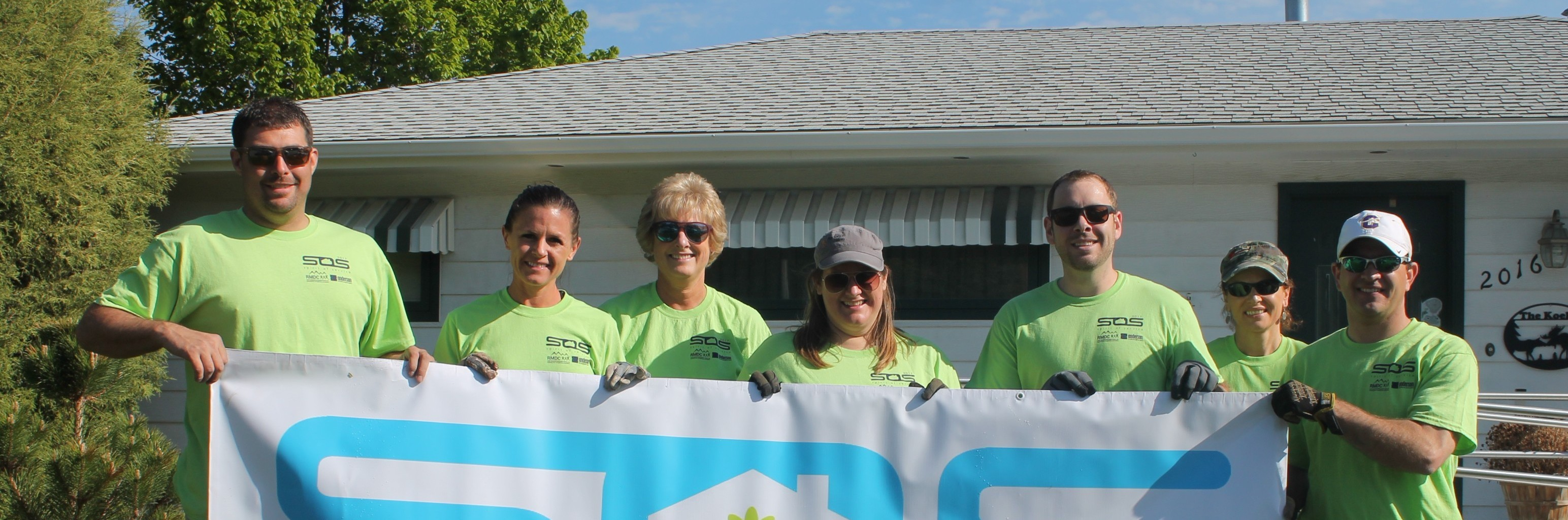 Pictured: Spirit of Service volunteers from First Interstate Bank with the SOS banner in front of a house.