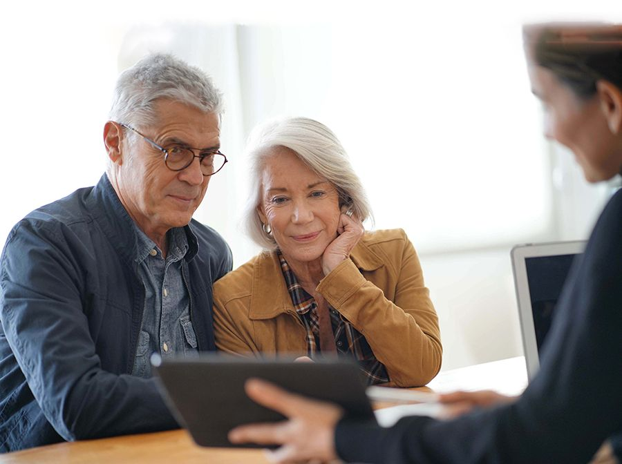 Older heterosexual couple meeting with a male advisor, looking at a tablet