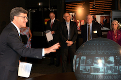 Jonathan Freed demonstrates using the Magic Planet at the NCM exhibit opening.