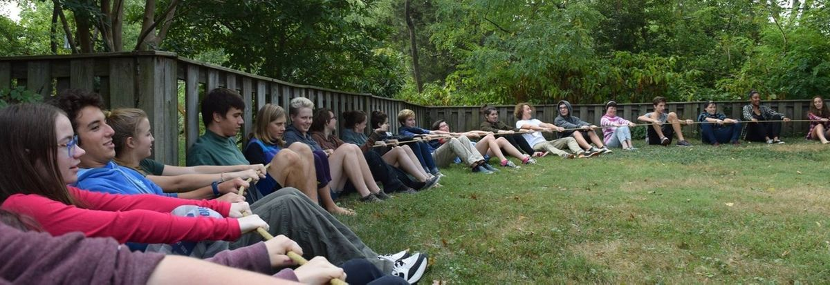 YFs sitting in a circle on a large lawn, pulling a rope to form the circle they are sitting in