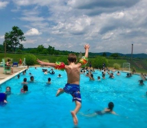 A camper jumps into the pool with his arms in the air.