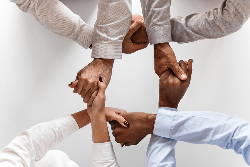 image of four people's hands, men and women with different colors of skin, wearing business shirts, grasping each other in a symmetrical manner, seen from above