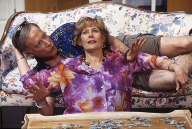 J. Martin is laying down on a couch, wearing a Hawaiian shirt and brown shorts with sunglasses on his forehead. Karen is kneeling in front of a couch, wearing a Hawaiian shirt while she's holding onto J. Martin in a nervously way.