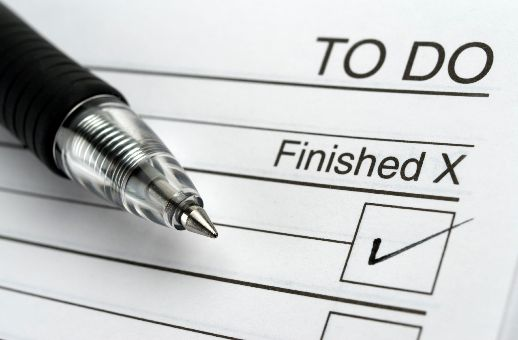 Ballpoint pen rests on to-do list with item checked off.