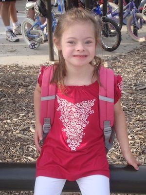 Little girl with Down syndrome at school with a backpack on her back.