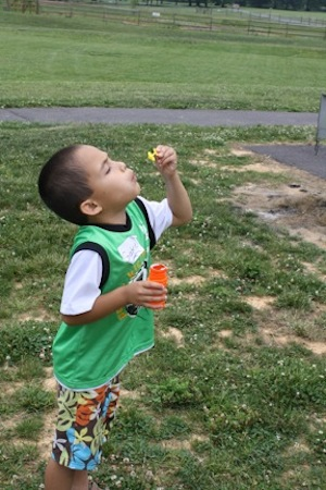 Cute boy blowing bubbles