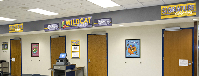 Cafeteria signs above entrance doors, purple and gold with food characters, menu board, line signs