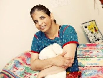 Woman supported by PSRS sitting on the edge of her bed, hugging a stuffed animal near her chest and smiling