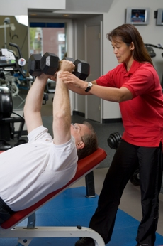 Photo of a PTP personal trainer helping a client with an exercise doing dumbell flyes on an inclined bench.