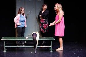 Three friends in a women's locker room, one wearing a pink sweater, the other person is wearing a black dress with flowers. The last person is wearing a pink towel and she's pointing about a prosthetic leg on the bench.