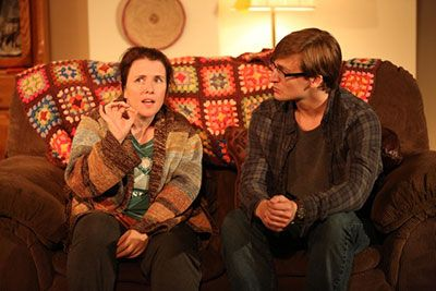 (L to R): Mary Theresa Archbold is wearing a multi-color sweater and John McGinty is wearing glasses and dark brown shirt with jeans. They are sitting on the couch and they are talking.