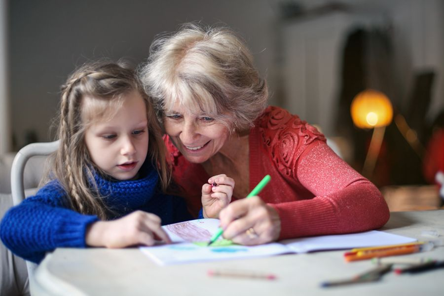 Smiling older woman sitting at the kitchen table with her young granddaughter. They're coloring pictures together.