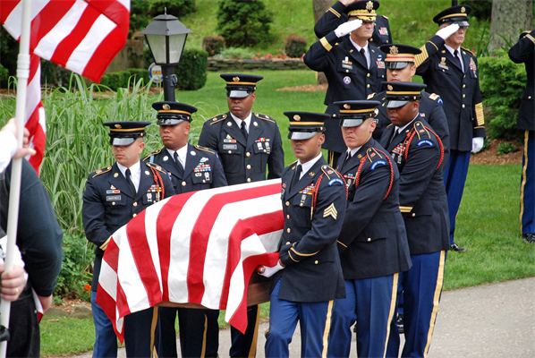 A military honor guard carries the flag draped casket of a fallen soldier