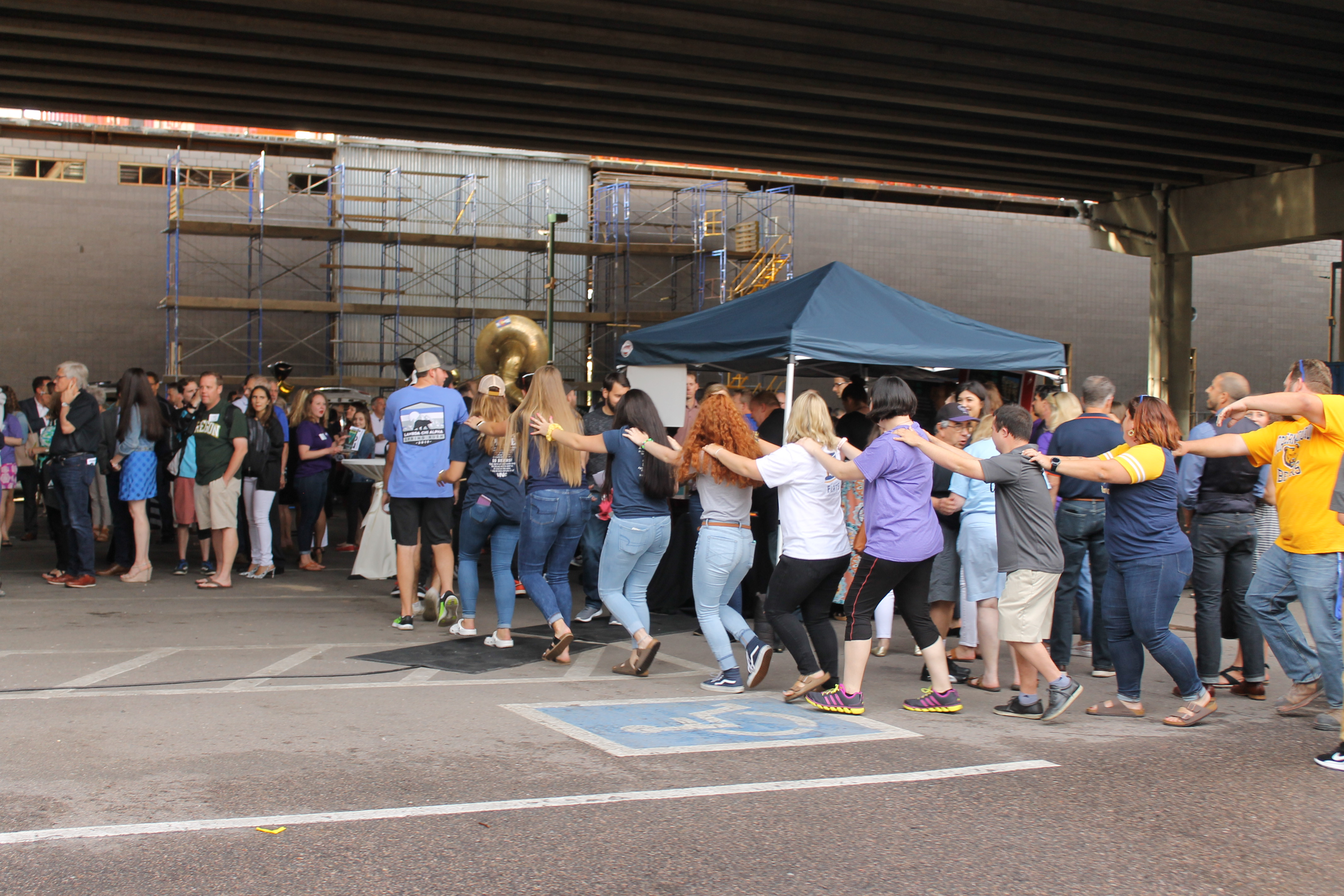 Group of people form a congo line in a parking lot